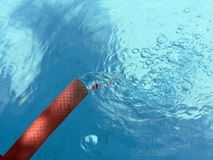 Hose water pouring into pool Stock Photography