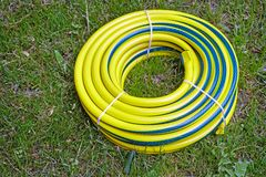 Hose for watering the garden. In the garden lies coiled in the form of a round plastic water hose for watering plants in the garden and the vegetable garden royalty free stock image