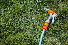 Hose for watering. With a nozzle lying on the green grass Stock Photography