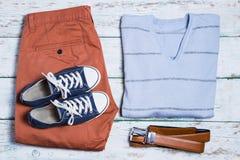 Hosen, Schuhe, Hemd und Gurt auf weißem Weinlesehintergrund Stockfotografie