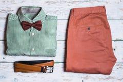Hosen, Schuhe, Hemd und Gurt auf weißem Weinlesehintergrund Lizenzfreie Stockbilder