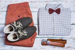 Hosen, Schuhe, Hemd und Gurt auf weißem Weinlesehintergrund Lizenzfreies Stockbild