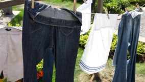 Hosen, Tücher, Leinen nach waschendem Fall auf einem Seil zwischen den Bäumen, getrocknet im Garten stock video
