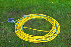 Hosepipe on grass. Yellow plastic hosepipe on grass lawn Stock Photo