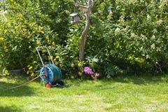 Hosepipe reel in the beautiful garden. Hosepipe reel in the beautiful, green garden bathed in sunlight stock images