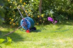 Hosepipe reel in the beautiful garden. Hosepipe reel in the beautiful, green garden bathed in sunlight royalty free stock photos