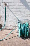 Hosepipe in the sunny garden. Next to a bright white wall Royalty Free Stock Image