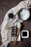 Hosomaki sushi on plate with soy sauce, bowl of rice and sesame seeds on table Stock Photos