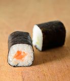 Hosomaki sushi. Sushi Hosomaki with salmon and green pepper on a wooden plate Royalty Free Stock Image