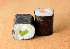 Hosomaki sushi. Sushi Hosomaki with salmon and green pepper on a wooden plate Stock Photography