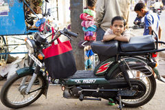 HOSPET, ÍNDIA - 20 de fevereiro de 2013 - menino indiano bonito no velomotor fotos de stock royalty free