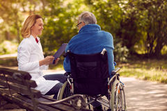 Hospice checking up the history of the patient in wheelchair. Hospice nurse checking up the history of the patient in wheelchair Stock Image