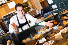 Hospitable man with delicious cream pies. At bakery display Stock Photo