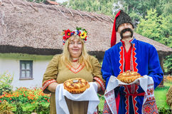 Hospitable man and woman in the Ukrainian national costumes Royalty Free Stock Photos