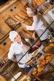 Hospitable women at bakery display Royalty Free Stock Image