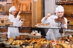 Hospitable women at bakery display Stock Photography