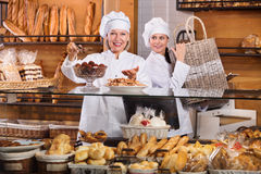 Hospitable women at bakery display Stock Images