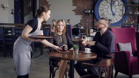 Hospitable young waitress bringing beverage in brown ceramic mug to the table for woman. Couple sitting at the
