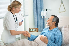 In hospital. Doctor talking to senior patient  lying in bed in hospital Stock Images
