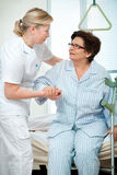 In hospital. Nurse helps a patient to get up in hospital Royalty Free Stock Photo