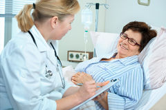 In hospital. Doctor or nurse talking to senior patient  lying in bed in hospital