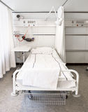 Hospital bed. One white hospital bed in a room Stock Photo