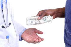 Hospital bill. Closeup of hand of uninsured patient paying cash to hand of medical doctor wearing lab coat on white background Stock Photos