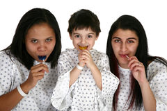 Hospital Buddies. Three young patients in hospital gowns with lolipops Royalty Free Stock Photo