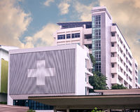 Hospital building with big symbolic at cloudy day Royalty Free Stock Image