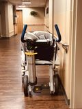 Hospital chair wheelchair in hall. Hospital chair wheelchair sitting in hallway at clinic with oxygen tank royalty free stock photos