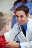 Hospital: Coração do doutor Listens To Boy na sala do exame imagens de stock
