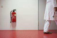 Hospital corridor and fire extinguisher red hand. Hospital with corridor fire extinguisher and doctor blurred as detail with stethoscope in hand n Central stock images