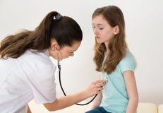 Hospital del doctor Examining Girl In foto de archivo libre de regalías