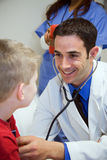 Hospital: Doctor Listens To Boy's Heart In Exam Room Stock Images