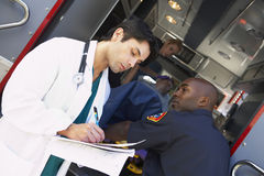 Hospital doctor taking notes paramedics Royalty Free Stock Image