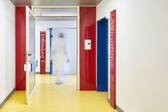 Hospital door delivery doctor corridor. Hospital with hallway and door for delivery on a ward with doctor blurred with wall red royalty free stock images