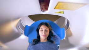 Hospital emergency MRI image scan. Woman lays in Magnetic Resonance Image device during medical exam. 4K.