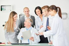 Hospital employee staff and doctors. Hospital employee staff and team of doctors discuss document Royalty Free Stock Image
