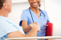 Hospital: A enfermeira e o paciente agitam as mãos imagem de stock