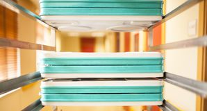 Hospital food trays. Trays of food in cage in hospital corridor royalty free stock image