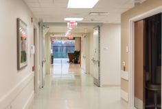 Hospital hallway with bright flourescent lights. Hospital hallway with bright flourescent lighting, clean sterile environment Stock Photo