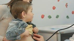 Hospital: Muchacho de los jóvenes del doctor Checks Heartbeat Of almacen de metraje de vídeo