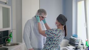 Hospital nurse is preparing and dressing a patient before orthodontic surgery. Nurse is preparing and dressing the patient to sterile clothe and putting medical stock footage