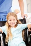 Hospital: Nurse Pushes Girl with Pigtails in Wheelchair royalty free stock photography