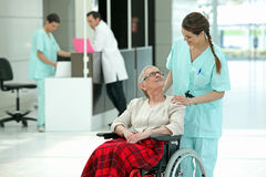 Hospital nurse pushing a patient. Hospital nurse pushing an elderly lady in a wheelchair Stock Photography