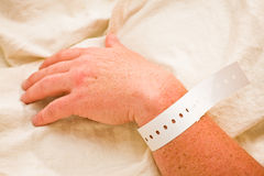 Hospital patient's hand with wristband royalty free stock image