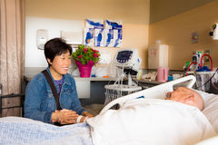 Hospital Patient Visitor. A middle aged Asian women sits at the bedside and holds hands with an elderly white male lying in a hospital bed Stock Photos