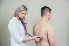 Hospital: Physician Checks Patient With Stethoscope Stock Image