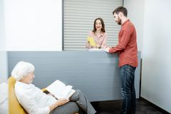 Hospital reception with clients. Modern hospital reception with senior women and men waiting for the doctor stock photo