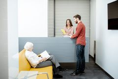 Hospital reception with clients. Modern hospital reception with senior women and men waiting for the doctor royalty free stock image